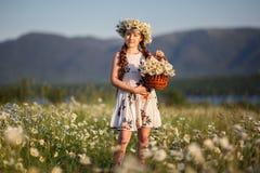 Милая девушка ребенка на поле стоцвета с корзиной цветков Стоковое фото RF