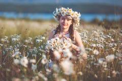 Милая девушка ребенка на поле стоцвета с корзиной цветков Стоковая Фотография