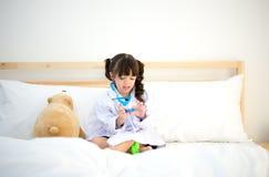 Милая девушка ребенк играя доктора с игрушкой плюша Стоковое Изображение RF