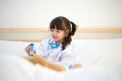 Милая девушка ребенк играя доктора с игрушкой плюша Стоковые Фото