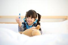 Милая девушка ребенк играя доктора с игрушкой плюша Стоковая Фотография RF