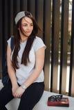 Милая девушка сидит на шагах и прочитала книгу с наушниками Стоковое Изображение RF