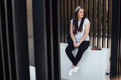 Милая девушка сидит на шагах и прочитала книгу с наушниками Стоковое Изображение