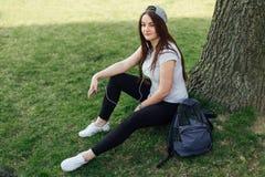 Милая девушка сидит на шагах и прочитала книгу с наушниками Стоковые Изображения RF