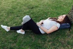 Милая девушка сидит на шагах и прочитала книгу с наушниками Стоковые Фото