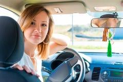 Милая девушка сидя в автомобиле за колесом Стоковое фото RF