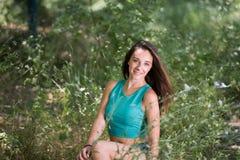 Милая девушка сидя на лестницах среди зеленой травы стоковое изображение