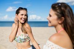 Милая девушка сидя на пляже с смеяться над друга Стоковые Изображения