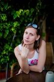 Милая девушка сидя на таблице Стоковые Изображения RF