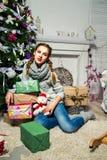 Милая девушка сидя около рождественской елки в белой комнате Новый y Стоковое фото RF