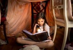Милая девушка сидя под одеялом и читая книгу Стоковое Изображение