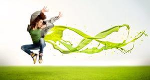 Милая девушка скача с зеленым абстрактным жидкостным платьем Стоковые Изображения RF