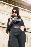 Милая девушка смотря ее телефон и отправляя СМС сообщение на социальные средства массовой информации стоковые изображения