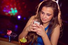 Милая девушка смотря smartphone Стоковое Фото
