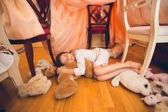 Милая девушка спать на поле с игрушками на спальне Стоковые Изображения