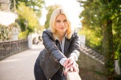 Милая девушка стоя на склонности моста на перилах Стоковые Изображения