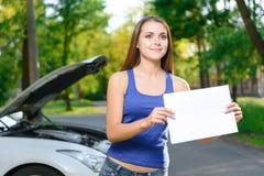 Милая девушка стоя с листом бумаги стоковые фото