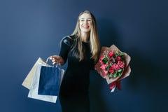 Милая девушка с букетом красных тюльпанов и пакетов Стоковая Фотография RF