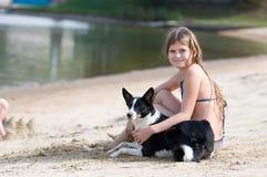 Милая девушка с ее собакой на пляже Стоковые Изображения