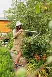 Милая девушка с длинными волосами делает вырезывание с большими ножницами сада стоковая фотография rf