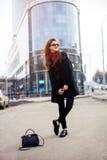 Милая девушка с длинными губами стиля причёсок и красного цвета в солнечных очках идет на улицу с сумкой Она усмехается и смотрит Стоковое Изображение