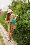 Милая девушка с длинным boxwood вырезывания волос с электрическим триммером изгороди стоковые фотографии rf