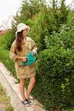 Милая девушка с длинным boxwood вырезывания волос с электрическим триммером изгороди стоковая фотография