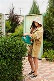 Милая девушка с длинным boxwood вырезывания волос с электрическим триммером изгороди стоковые фото