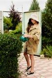 Милая девушка с длинным boxwood вырезывания волос с электрическим триммером изгороди стоковое изображение