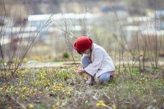 Милая девушка с отрезками провода в шляпе собирая желтые цветки Стоковые Изображения RF