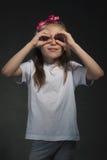 Милая девушка с пальцами вокруг глаз стоковые фото