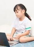 Милая девушка с ПК компьтер-книжки дома Стоковое Изображение RF