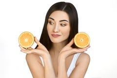 Милая девушка с 2 половинами апельсина в руках на белой предпосылке Стоковое Изображение RF
