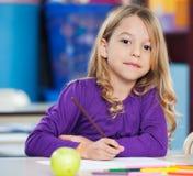 Милая девушка с ручкой эскиза и бумага на столе Стоковое Изображение