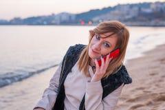 Милая девушка с телефоном на пляже Стоковые Фото
