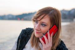 Милая девушка с телефоном на пляже Стоковые Фотографии RF