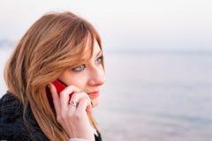 Милая девушка с телефоном на пляже Стоковые Изображения