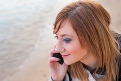 Милая девушка с телефоном на пляже Стоковая Фотография
