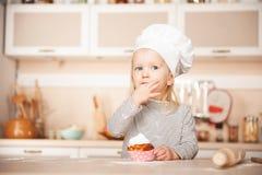 Милая девушка с тортом дегустации шляпы шеф-повара в кухне Стоковые Фотографии RF