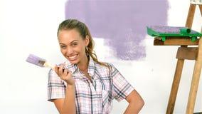 Милая девушка с щеткой в руке усмехаясь на камере сток-видео