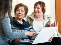 Милая девушка уча положительным усмехаясь старшим женщинам используя компьтер-книжку Стоковые Фото