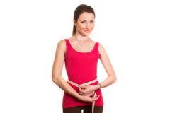 Милая девушка фитнеса измеряя ее изолированную талию Стоковые Фотографии RF
