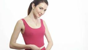 Милая девушка фитнеса измеряя ее изолированные талию и усмехаться акции видеоматериалы