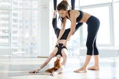 Милая девушка redhead практикуя воздушную йогу с личным тренером Стоковая Фотография