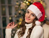 Милая женщина брюнет в шляпе Санты около рождественской елки Стоковые Изображения RF