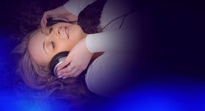 Милая женщина в больших наушниках слушая к музыке и голубому свету Стоковые Изображения RF