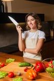 Милая женщина в кухне при нож смотря к камере стоковая фотография
