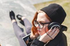 Милая женщина в музыке черных одежд слушая в наушниках на улице и смотреть прочь стоковые фотографии rf
