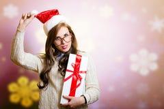Милая женщина в шляпе Санты держа giftbox дальше Стоковые Изображения