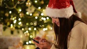 Милая женщина в шляпе Санты используя черный Smartphone и усмехаться на рождественской елке предпосылки Красивая девушка в крышке